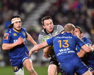 All Black fullback Ben Smith looks to burst through the tackle of Otago centre Matt Faddes as...
