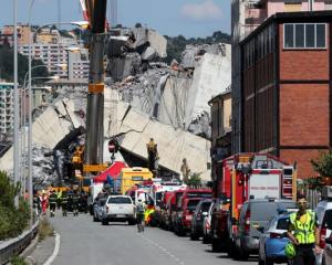 Firefighters and rescue workers stand at the site of a collapsed Morandi Bridge. Photo: Reuters