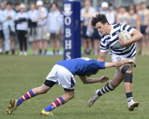 Otago Boys' High School centre Jake Te Hiwi tries to outstep Southland Boys' High School opposite...