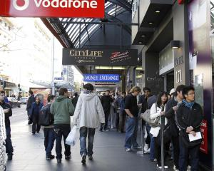 People queue on Auckland's Queen St waiting to be let into a Vodafone store to buy an iPhone 4....