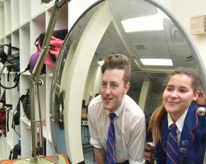 St Peter's College pupils Mia Walton (16) and Wyatt Simon (17) see how light behaves in a...