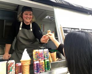 Patti's & Cream owner Olive Tabor serves an ice cream sample from her food truck to...