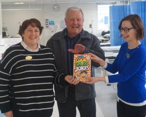 Mosgiel resident Warren Wenlock (centre) hands over a joke book to Bowel Screening nurse co...