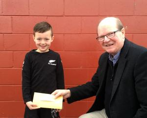 Mason Dunphy gives Taieri Facilities Community Trust member Bill Feather $280 on Tuesday to help...