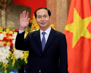 Vietnamese President Tran Dai Quang greets journalists as he waits for the arrival of Russian...