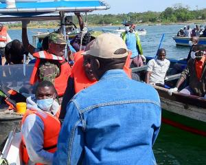 Rescuers search the water after the ferry overturned off the shores of Ukerewe Island on Lake...