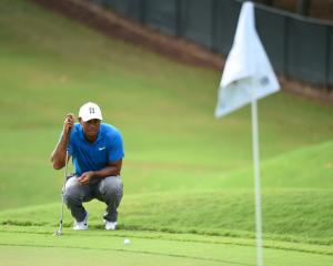 Tiger Woods lines up a shot on the 11th green during the third round of the Tour Championship....