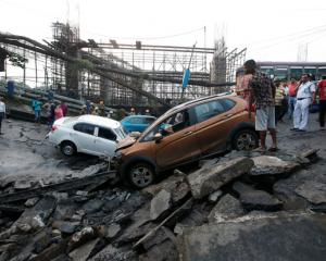 People stand next to the wreckage of vehicles at the site of a bridge that collapsed in Kolkata....