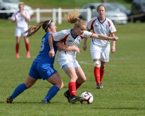 Southern United's Chelsea Whittaker attempts to take the ball off Auckland's Paige Satchell...