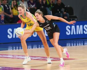 Jane Watson attempts to control the ball for the Silver Ferns as Australia's Caitlin Bassett...
