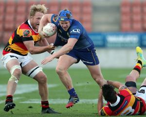 Otago loose forward James Lentjes takes on Waikato defenders James Tucker (left) and Jordan...