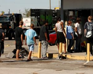 People wait in line to enter a convenience store in Callaway, Florida after Hurricane Michael hit...