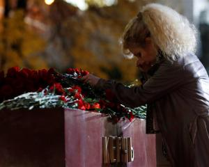 A woman lays flowers at a memorial by the Kremlin walls in Moscow to commemorate the victims of...