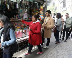 Customers line up to buy Mega Millions tickets at a newsstand in midtown Manhattan in New York....