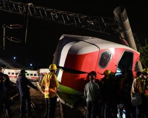 Rescue workers at the scene after the train dereailed. Photo: Reuters