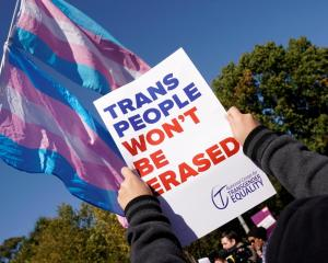 Activists protest the US government's alleged attempt to strip transgender people of official...