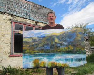 Central Otago Art Society president Nigel Wilson displays one of his artworks before the...