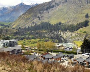 The Shotover Jet heads upriver below new housing at Arthurs Point, near Queenstown. Photo:...