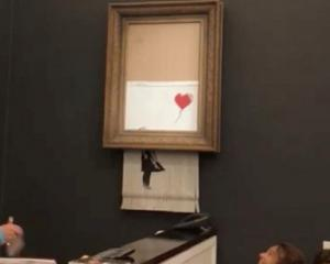 "Banksy's painting ""Girl with Red Balloon"" is seen shredded after its sale at Sotheby auction in..."