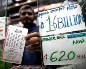 A newsstand vendor displays tickets for the Mega Millions lottery drawing in the USA. Photo: Reuters