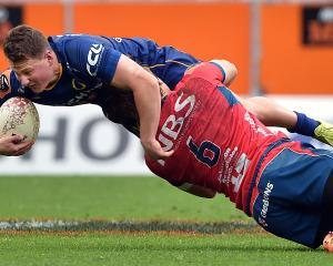 Otago first five-eighth Finn Strawbridge is tackled by Tasman flanker Ethan Blackadder during a...