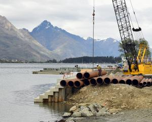 A crane moves pipes at the Frankton marina site. Photo: Stephen Jaquiery