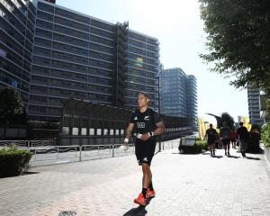 All Black halfback Aaron Smith walks back to the team bus after an All Black gym session in Tokyo...