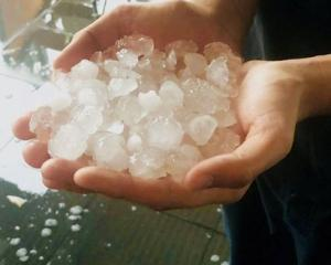 A person holds a sample of the hailstones that fell in Queensland during a storm. Photo: ...