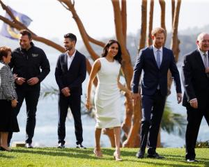Britain's Prince Harry and wife Meghan, Duchess of Sussex walk with Australia's Governor General...