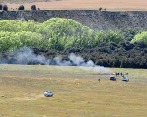 Smoke rises from the wreck of a helicopter crash near Wanaka Airport earlier today. Photo: Mark...