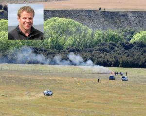 Smoke rises from the wreck of a helicopter crash near Wanaka Airport earlier today. Photo: Mark Price INSET: Nick Wallis