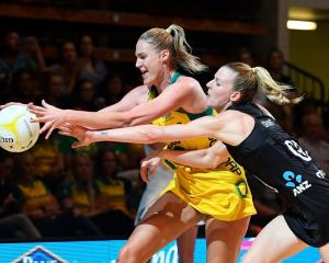 Australia's Caitlin Bassett competes with the Silver Ferns' Katrina Grant for the ball during...