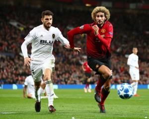 Marouane Fellaini of Manchester United is challenged by Cristiano Piccini of Valencia during...