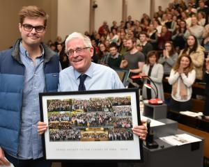 Law student Tim Austen presents lecturer Prof Mark Henaghan with a board of finalists' pictures...