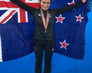New Zealand cyclist Natasha Hansen celebrates with the New Zealand flag after winning a bronze...