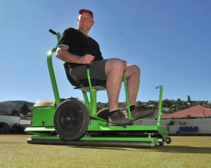 Jim Scott hard at work yesterday on the North East Valley Bowling Club greens, before its Labour...