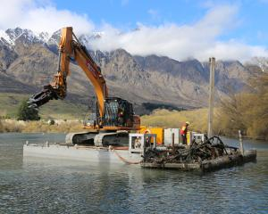 An excavator on a barge removes submerged trees from the Kawarau River near Frankton. Photos:...