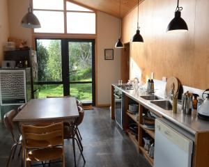 The kitchen-dining area has glass doors at both ends, visually expanding the space into the...