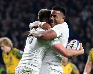England's Owen Farrell (L) celebrates with Manu Tuilagi after scoring their fourth try. Photo:...
