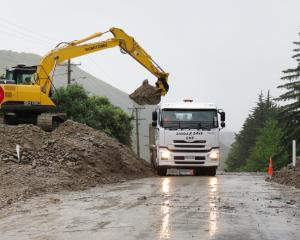 A digger clears debris from a culvert on State Highway 8, near the Roxburgh golf course early this morning, following heavy rain last night. Photo: Yvonne O'Hara
