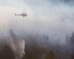 Four helicopters used monsoon buckets to fight the blaze. Photo: Andy Cole