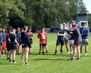 Brisbane Broncos game development officer Jack Reed with a group of young players at a training...