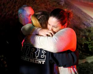 People comfort each other after a mass shooting at a bar in Thousand Oaks. Photo: Reuters