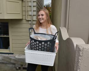 Student Chloe Hedges (20) carries her belongings to a removal truck yesterday morning. PHOTO:...
