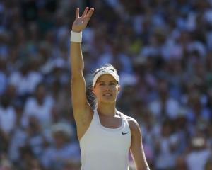 Eugenie Bouchard of Canada waves after defeating Simona Halep of Romania in their women's singles...