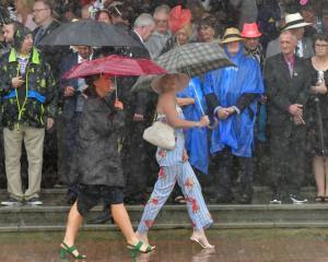 Racegoers brave the rain at Flemington Racecourse. Photo: Getty