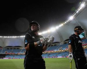 New Zealand batsmen George Worker and Henry Nicholls leave the field as rain stops play during...