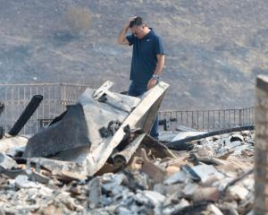 A Bell Canyon resident looks over the rubble of his burned-down home. Photo: Getty Images