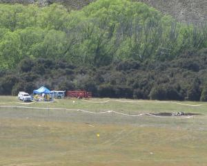 Investigators search the area around the wreckage of the Hughes 500 which lies under the blue...