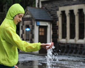 Odin Jacobs (14) releases a handful of hail after a heavy bout in Dunedin today. Photo: Alison...